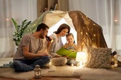 Glückliches Familienlesebuch im Kinderzelt zu Hause lizenzfreie stockfotografie
