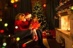 Glückliches Familienlesungsweihnachtsbuch, das an sitzt Stockfoto