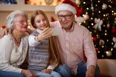 """Glückliches Familienmomente †""""Enkelin, die selfie mit smartp nimmt Lizenzfreie Stockfotografie"""