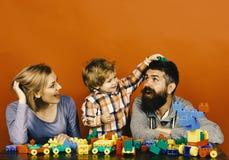 Glückliches Familienspiel Familie mit Gestalt der fröhlichen Gesichter aus farbigen Baublöcken heraus lizenzfreie stockfotografie
