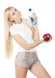 Glückliches fitnesswoman mit Wasser und rotem Apfel Lizenzfreies Stockfoto