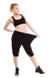 Glückliches Frauendarstellen, wie viel Gewicht sie verlor, große Hosen Lizenzfreie Stockfotos