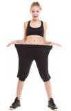 Glückliches Frauendarstellen, wie viel Gewicht sie verlor, große Hosen Lizenzfreie Stockbilder