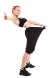 Glückliches Frauendarstellen, wie viel Gewicht sie verlor, große Hosen Stockfotos
