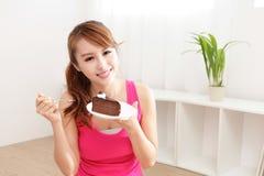 Glückliches Frauenlächeln, das Schokoladenkuchen isst Lizenzfreies Stockbild