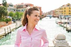 Glückliches Frauenlächeln, untersuchend Abstand auf Brücke in Venedig Lizenzfreies Stockfoto