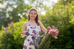 Glückliches Frauenreiten-fixie Fahrrad im Sommerpark Stockfotografie