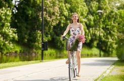 Glückliches Frauenreiten-fixie Fahrrad im Sommerpark Stockfotos