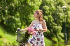 Glückliches Frauenreiten-fixie Fahrrad im Sommerpark Stockbilder