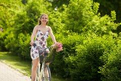 Glückliches Frauenreiten-fixie Fahrrad im Sommerpark Lizenzfreies Stockbild
