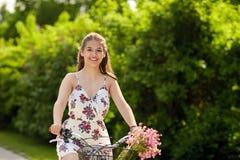 Glückliches Frauenreiten-fixie Fahrrad im Sommerpark Lizenzfreie Stockbilder