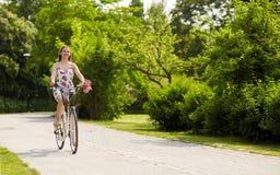 Glückliches Frauenreiten-fixie Fahrrad im Sommerpark Stockbild