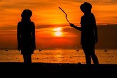 Glückliches Frauenschattenbild, das gegen Sonnenuntergang mit den Armen angehoben steht Stockbild