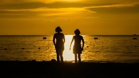 Glückliches Frauenschattenbild, das gegen Sonnenuntergang mit den Armen angehoben steht Stockbilder