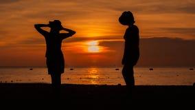 Glückliches Frauenschattenbild, das gegen Sonnenuntergang mit den Armen angehoben steht Lizenzfreie Stockfotos