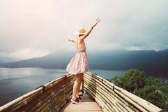 Glückliches Frauentanzen, das frei glaubt, reisend die Welt, die Arme zum Himmel anhebt stockfoto