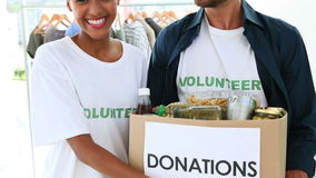 Glückliches freiwilliges Team, das einen Lebensmittelspendenkasten hält stock video