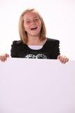 Glückliches freundliches jugendliches Mädchen, das ein Zeichen anhält stockfotos