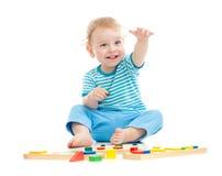 Glückliches freundliches Kind, das pädagogische Spielwaren spielt Stockbilder