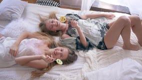 Glückliches Freundmädchen in den silk sleepwears essen süße Lutscher und sprechen das Lügen auf Bett am Morgen stock video footage