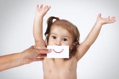 Glückliches frohes Baby, das eigenhändig ihr Gesicht mit dem Lächeln gezeichnet versteckt Lizenzfreies Stockbild