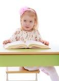 Glückliches frohes blondes Mädchen liest ein starkes Buch Stockfotos
