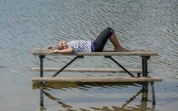 Glückliches frohes kleines Mädchen, das auf dem Picknicktisch bleibt im See liegt und sich entspannt Lizenzfreie Stockfotos