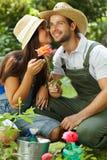 Glückliches Gartenarbeitpaarküssen stockfotos