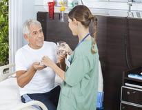 Glückliches geduldiges empfangendes Medizin-und Wasser-Glas von der Krankenschwester stockfotografie
