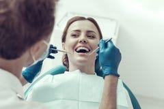 Glückliches geduldiges, ihren Zahnarzt betrachtend stockbilder