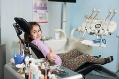 Glückliches geduldiges Mädchen, das sich Daumen im zahnmedizinischen Klinikbüro zeigt Medizin-, Stomatologie- und Gesundheitswese lizenzfreie stockfotografie