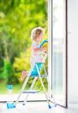 Glückliches gelocktes Mädchen, das ein Fenster im Reinraum wäscht Stockfoto