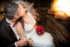 Glückliches gerade verheiratetes Paar, das nahe Kamin sitzt Lizenzfreies Stockbild
