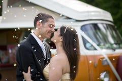 Glückliches gerade verheiratetes Paar in einem klassischen Reisemobil auf einem Gebiet Stockfoto