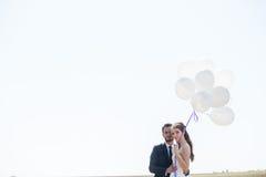 Glückliches gerade verheiratetes Paar mit Ballonen in der Hand Lizenzfreies Stockfoto