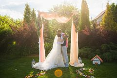 Glückliches gerade verheiratetes Paar am weichen Sonnenunterganglicht stockfotos