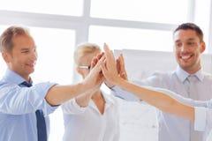 Glückliches Geschäftsteam, das Hoch fünf im Büro gibt Lizenzfreie Stockfotografie