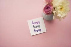 ` Glückliches ` geschrieben in Kalligraphieart auf Papier mit Blumenstrauß von Rosen und von Chrysanthemen auf einen rosa Hinterg Lizenzfreie Stockfotografie