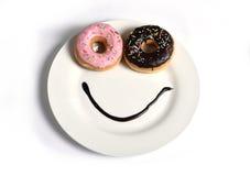 Glückliches Gesicht des smiley gemacht auf Teller mit Schaumgummiringaugen und Schokoladensirup als Lächeln im Zucker und in der  Stockfotos