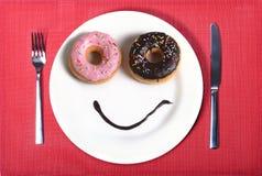 Glückliches Gesicht des smiley gemacht auf Teller mit Schaumgummiringaugen und Schokoladensirup als Lächeln im Zucker und in der  Lizenzfreies Stockbild