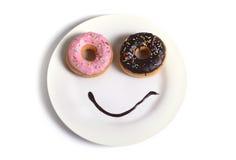 Glückliches Gesicht des smiley gemacht auf Teller mit Schaumgummiringaugen und Schokoladensirup als Lächeln im Zucker und in der  Stockfoto