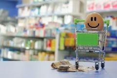 Glückliches Gesicht mit Geld und Warenkorb mit unscharfem Hintergrund Stockfoto
