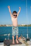 Glückliches gesundes nettes Kind, das oben seine Hände mit Glück anhebt Lizenzfreie Stockbilder