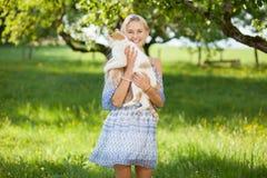 Glückliches gir auf einer Sommerblumenwiese, die eine Katze hält Stockbilder