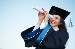 Glückliches graduiertes Mädchen, das durch schaut stockbild