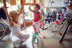 Glückliches Großmutter- und Mädchenkaufenfahrrad und -sturzhelme im Fahrradgeschäft stockbild