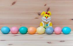 Glückliches Häschen mit acht Ostereiern auf dem hölzernen Stockfotografie
