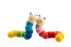Glückliches hölzernes Baby spielt die Würmer, die auf Weiß lokalisiert werden lizenzfreie stockbilder