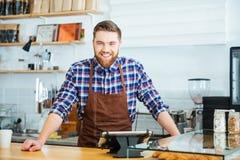 Glückliches hübsches barista im karierten Hemd und im braunen Schutzblech Stockbild