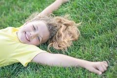 Glückliches hübsches Mädchen, das auf grünem Gras mit den ausgestreckten Armen liegt und am Sommer lächelt Stockbilder